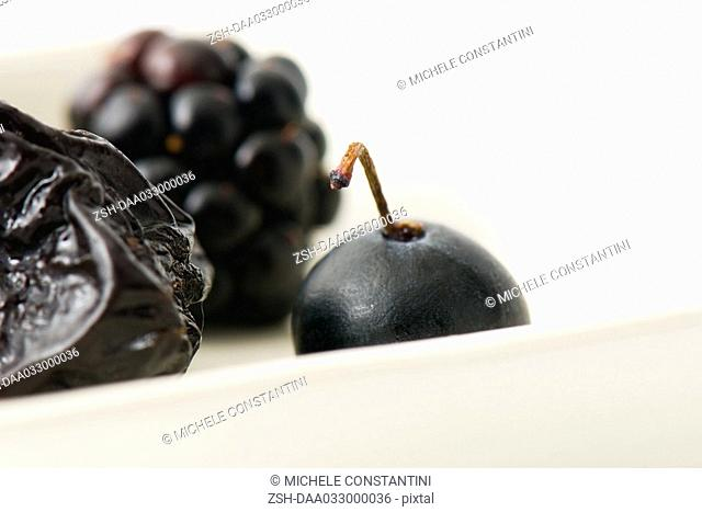 Prune, blackberry and blueberry on dish