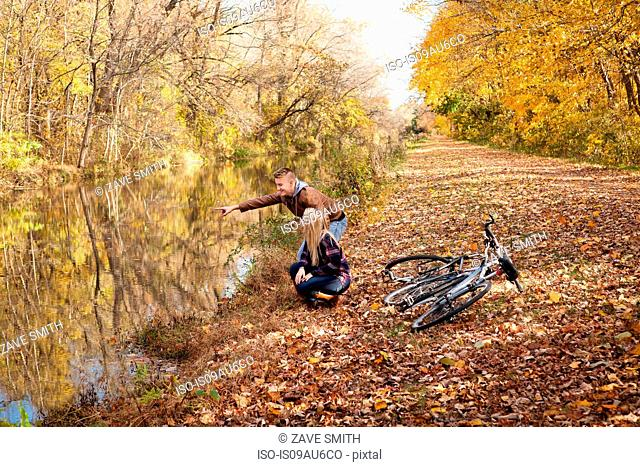 Teenage boy and adult sister pointing at river in autumn forest
