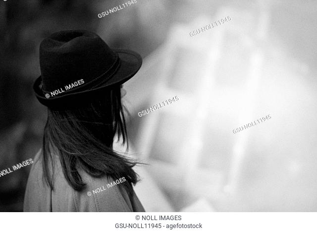 Young Woman Looking Away Wearing Black Hat With Brim