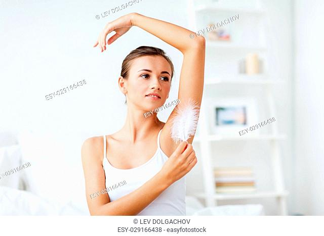 people, beauty, hygiene, depilation and epilation concept - beautiful woman sitting on bed and touching her armpit with feather at home bedroom
