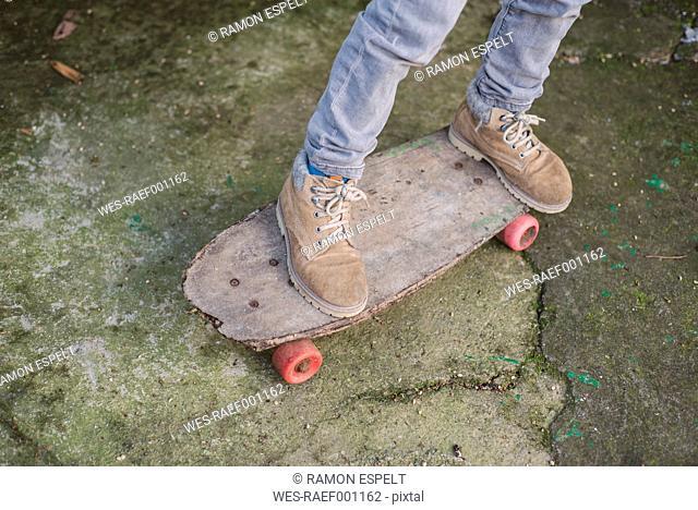 Legs of boy on an old skateboard