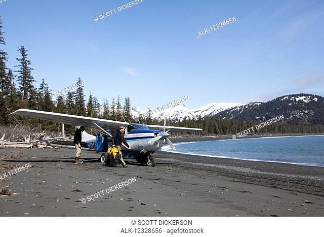 Surfers unloading gear from a Cessna 206 on the Kenai Peninsula Outer Coast, South-central Alaska; Alaska, United States of America