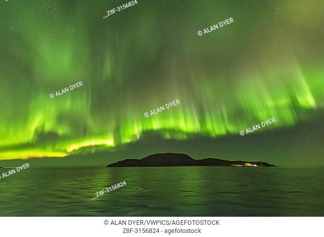 Curtains of aurora, some with a nitrogen pink fringe, arcing over an island along the Norwegian coast during a fine display on October 24, 2017