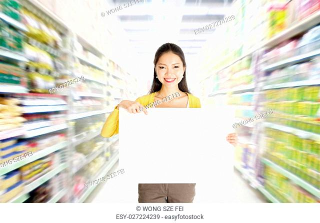 Young Asian woman hand holding a blank white paper card sign board in market or department store