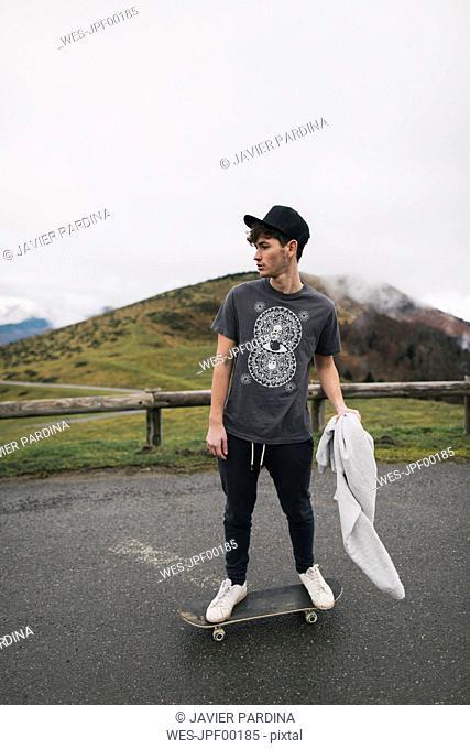 Spain, Lleida, young man on skateboard in rural landscape