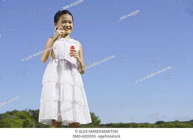 Girl in white dress, blowing bubbles