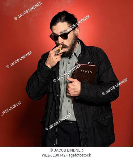 Man smoking cigar, holding a Lenin book