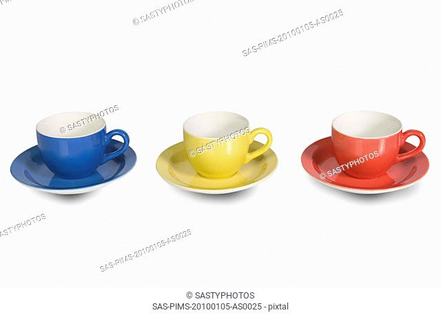 Colorful tea cups with saucers in a row