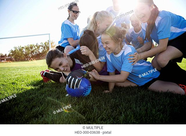 Playful middle school girl soccer team celebrating in pile on sunny field