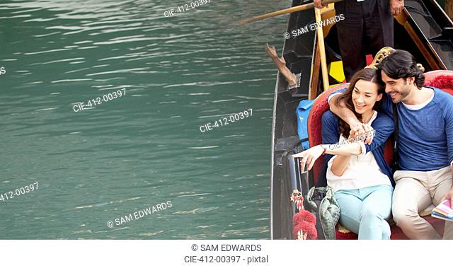 Smiling couple riding in gondola on canal in Venice