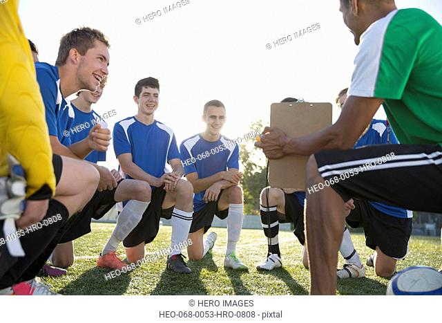 Soccer team smiling while listening to coach