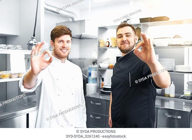 happy chefs at restaurant kitchen showing ok sign