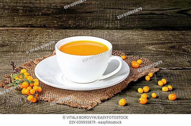 Tea of sea-buckthorn berries on wooden table with blurred background