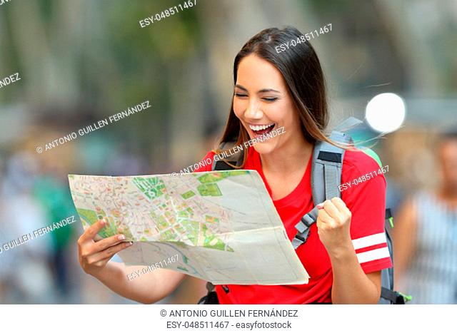 Excited teen tourist finding destination in a paper guide on the street