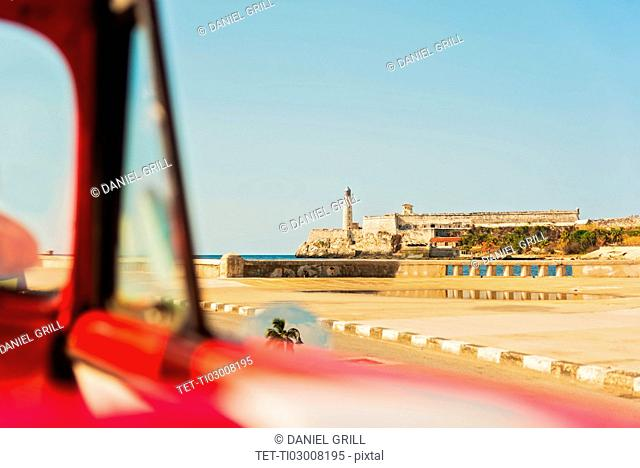Cuba, Havana, Fort with lighthouse seen from convertible