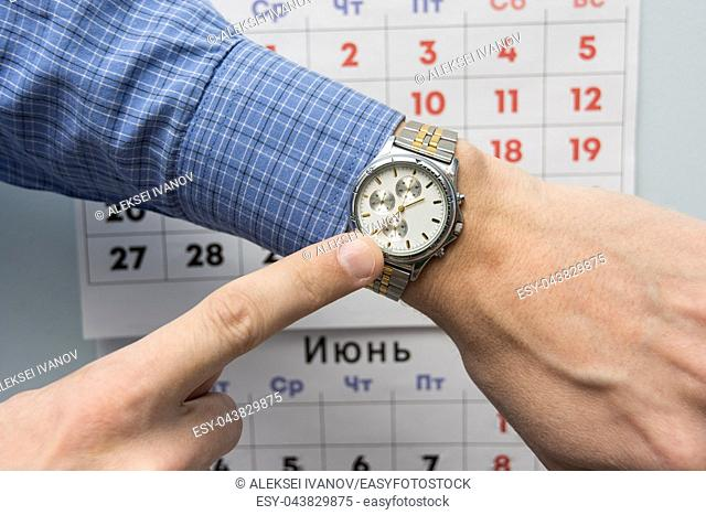 Office specialist's hand points to a wristwatch, in the background is a wall calendar