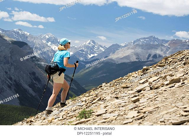 Female hiker with poles hiking up a rocky mountain ridge with valleys and mountains in the background with blue sky and clouds; Alberta, Canada