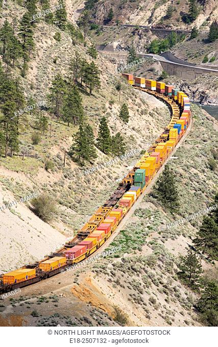 Canada, BC, Lytton. Train cars with shipping containers on the edge of steep valley in the Thompson River Canyon