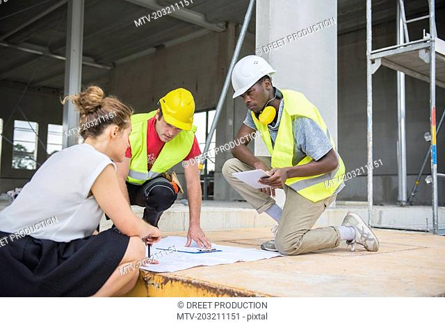 Architect discussing blueprint with construction workers at building site