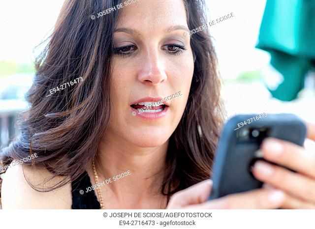 A pretty brunette woman looking down at her mobile phone