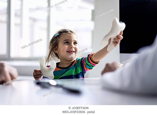 Portrait of smiling girl with tooth model at desk in medical practice