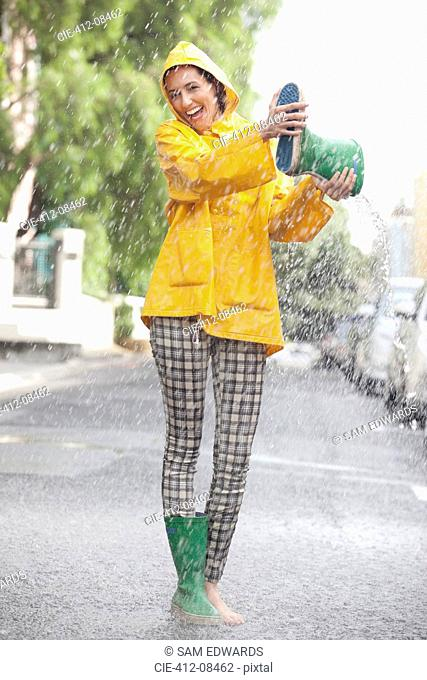 Portrait of enthusiastic woman emptying boot in rain