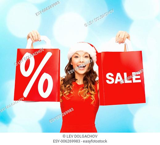sale, gifts, christmas, holidays and people concept - smiling woman in red dress with shopping bags and percent sign on them over blue lights background