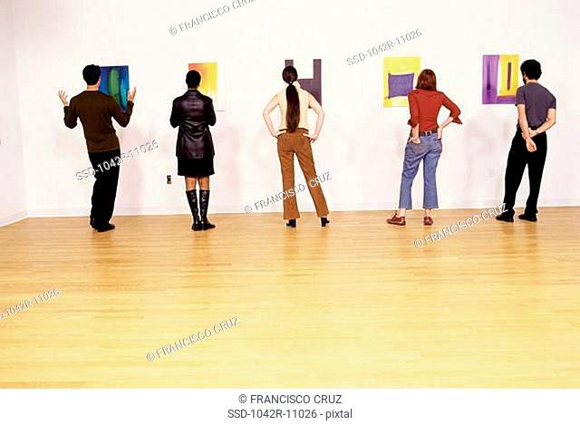 Group of people looking at paintings in an art gallery