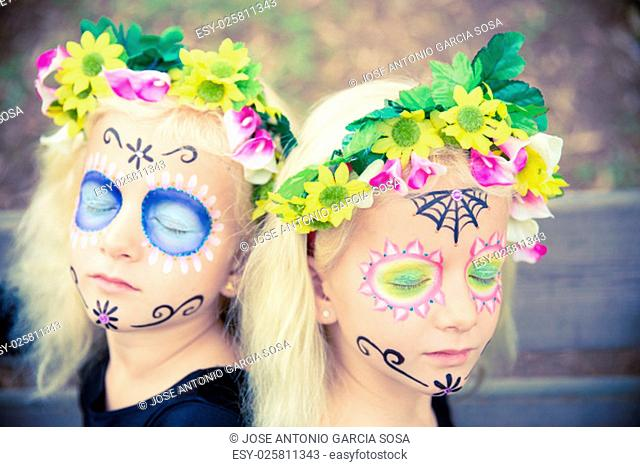 Twin girls with closed eyes in halloween costume outdoors