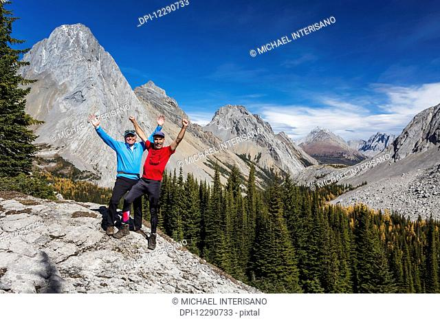 Two male hikers with arms raised in the air on rock ridge overlooking alpine valley with colourful larch trees in autumn and rocky peaks with blue sky and...