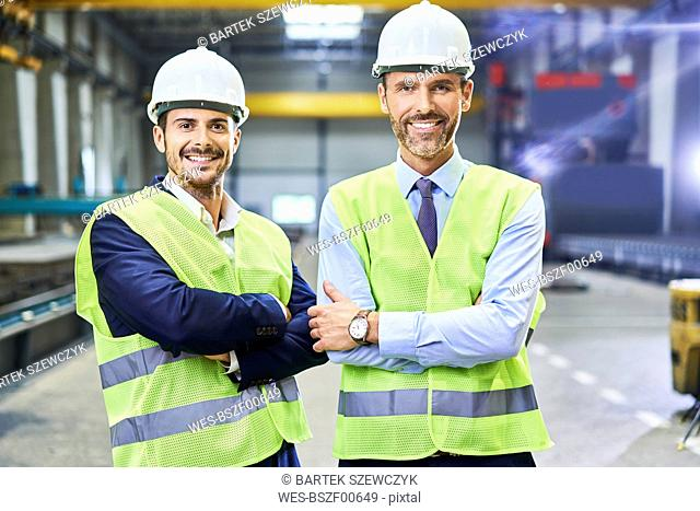 Portrait of two smiling managers wearing protective workwear in factory