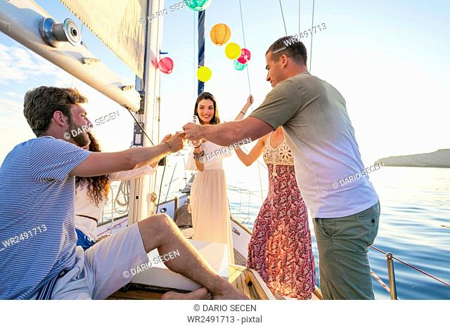 Friends toasting wine glasses on sailboat