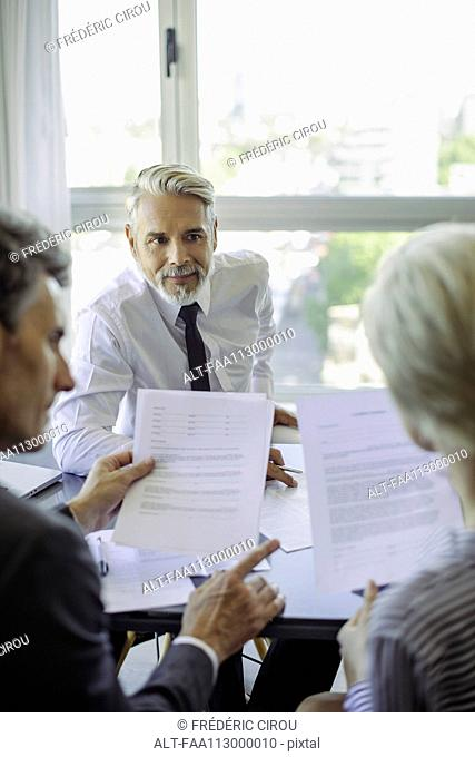 Couple reading document during meeting with businessman