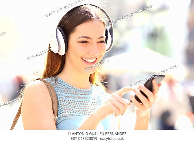 Happy girl listening to music browsing smart phone content walking in the street
