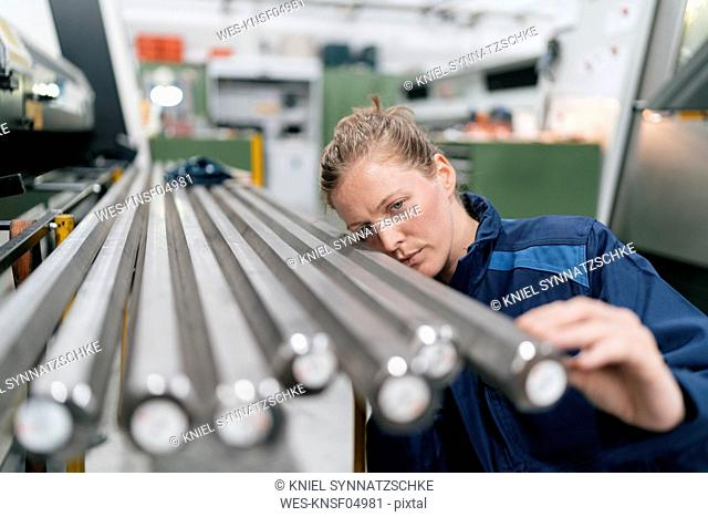 Young woman working as a skilled worker in a high tech company, checking steel rods
