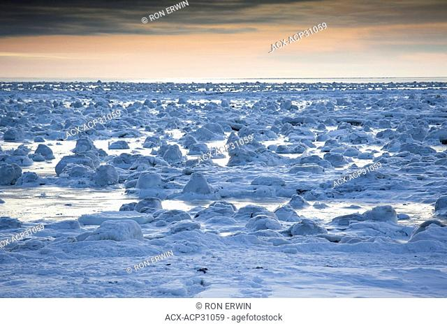 Dawn lights the ice and snow coating the rocks near the shore of Hudson Bay revealing a lumpy frozen landscape near the Seal River estuary north of Churchill