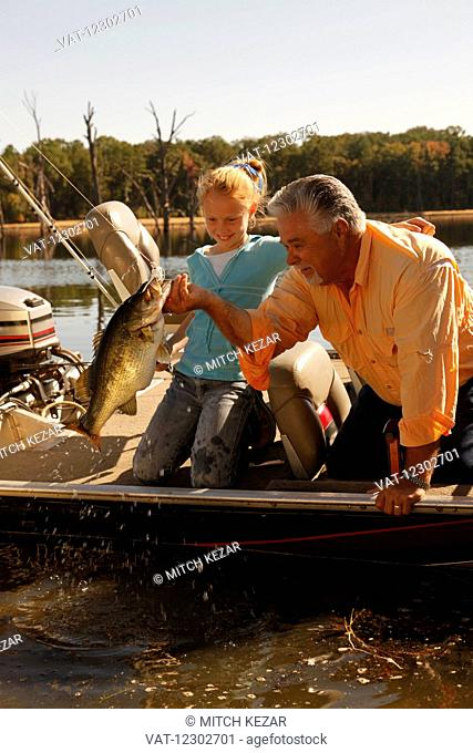 Grandfather And Grandson Fishing On Lake