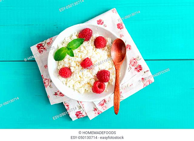 Ricotta with raspberries in a bowl on turquoise wooden background. Curd cheese, cottage cheese, tvorog. Healthy eating, healthy lifestyle