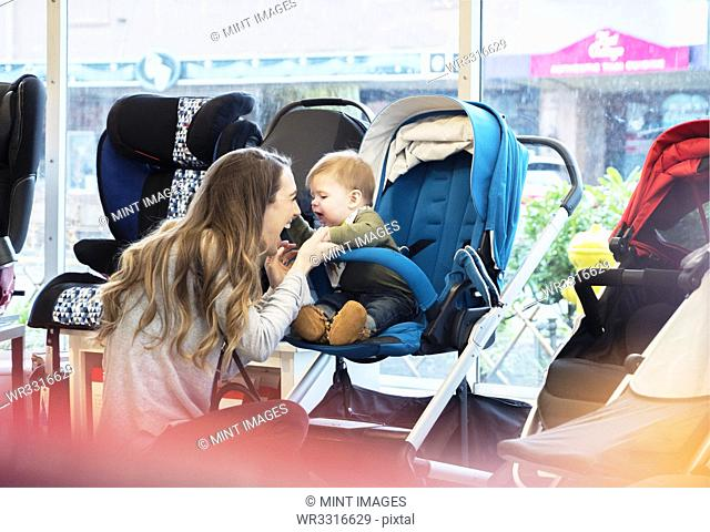 Caucasian mother and baby son shopping in stroller store