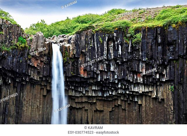 Black basalt faces framed by a jet of water. Magnificent waterfall Svartifoss in Icelandic Skaftafell park