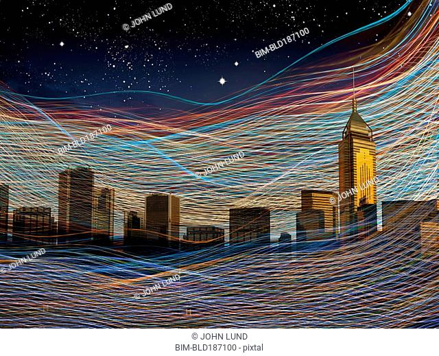 Light streams over city skyline at night sky