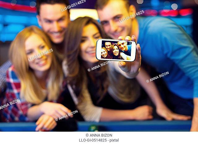 Smiling friends taking selfie photo from nightclub with billiard. Rzeszow, Poland