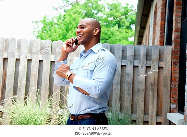 Mid adult man using mobile phone in garden, smiling