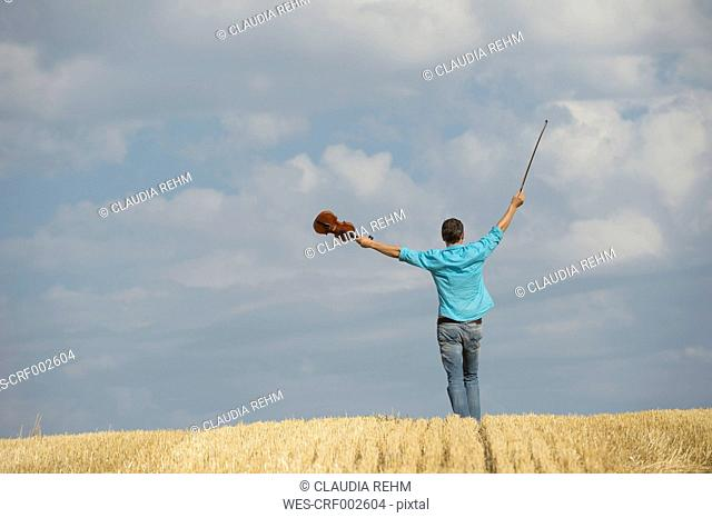 Germany, Bavaria, Starnberg Region, Man playing violin in field