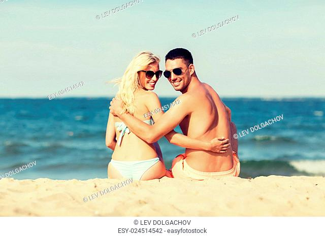 love, travel, tourism, summer and people concept - smiling couple on vacation in swimwear sitting on beach and looking back