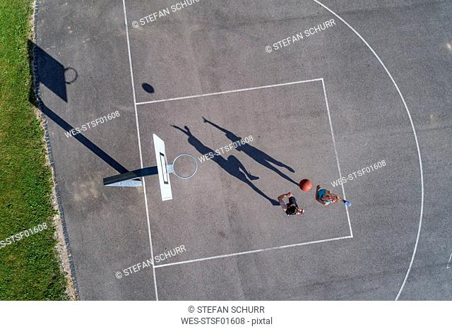 Young man and woman playing basketball, aerial view
