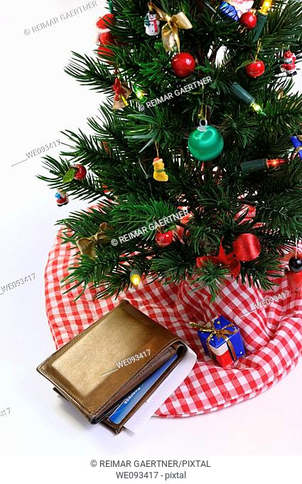 Worn wallet with charge cards and check under the decorated Christmas tree