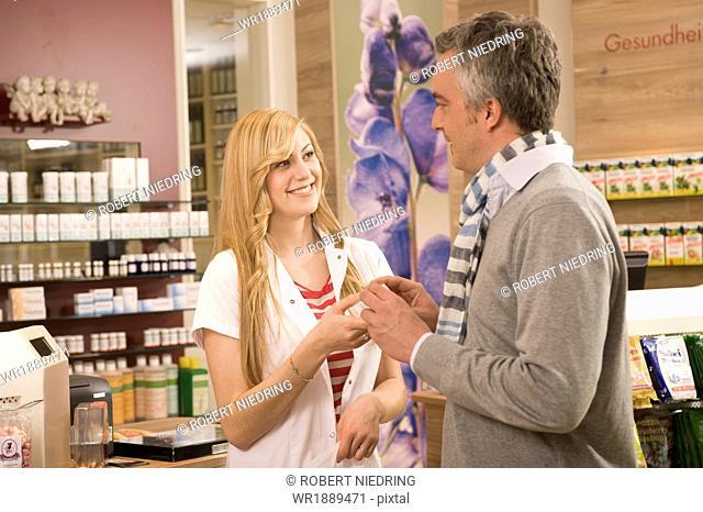 Female Pharmacist Talking To Customer, Munich, Bavaria, Germany