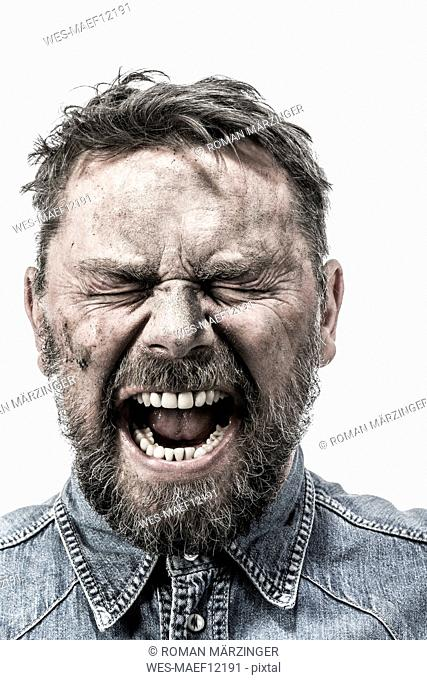 Portrait of screaming man with dirty face