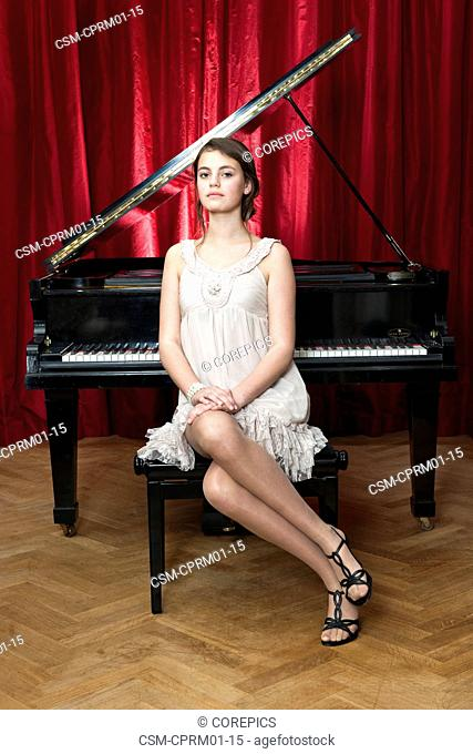 Portrait of a young pianist, posing in front of a black grand piano and a red curtain